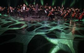 Toruńska Orkiestra Symfoniczka podczas koncertu noworocznego, na pierwszym planie światł oświetlają scenę