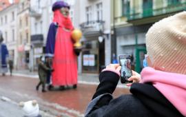 Olbrzymie figury trzech króli podążają ulicą Szeroką, na pierwszym planie osoba robiąca zdjęcie telefonem