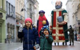 Dwoje małych dzieci stoi na ulicy Szerokiej, w tle figury trzech króli