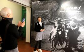 Mężczyzna robi zdjęcie kobiecie przy dużej fotografii czarnobiałej, przedstawiającej podróżników na koniach