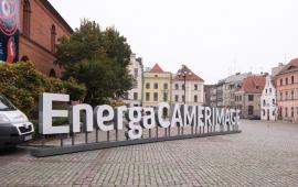 Napis EnergaCamerimage ustawiony na Rynku Nowomiejskim, w tle siedziba festiwalu - Fundacja Tumult
