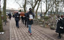 Na zdjęciu obsługa pogrzebu niesie trumnę na cmentarzu przy ul. Wybickiego