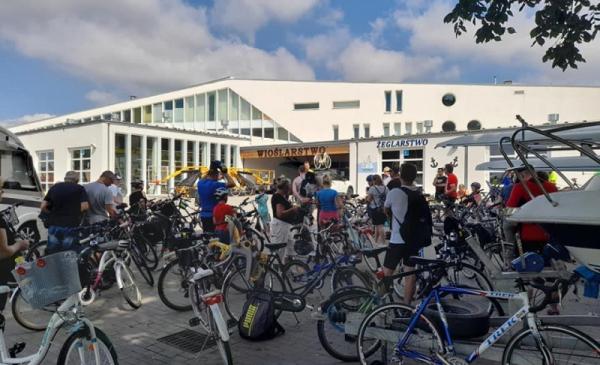 Rowerzyści stoją na tle Przystani Toruń