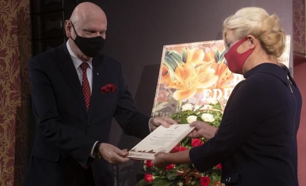 Prezydent Michał Zaleski - w maseczce - wręcza list gratulacyjny nauczycielce