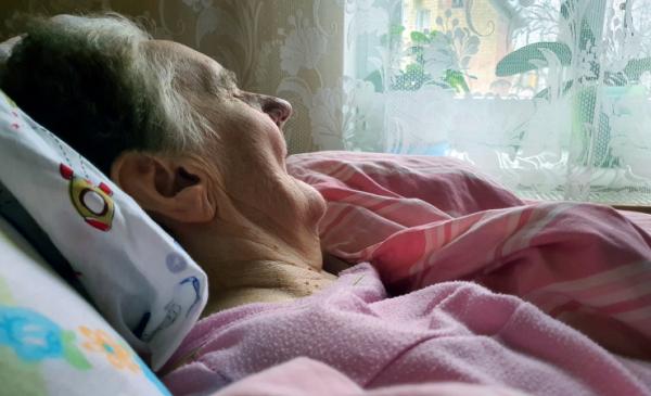 Starsza kobieta leżąca w łóżku