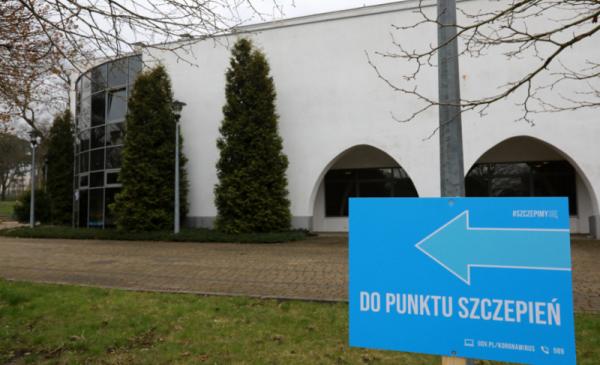 Na zdjęciu drogowskaz przed Centrum Targowym Park informujący o drodze do Punktu Szczepień Powszechnych. W tle budynek centrum.