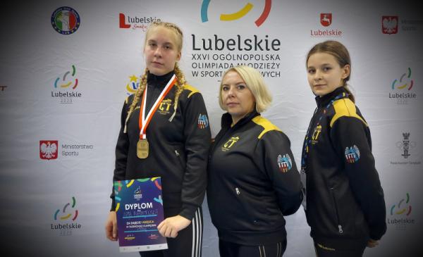 Mistrzyni taekwondo Maja Błażejewicz z medalem i dyplomem, z trenerką oraz drugą zawodniczką
