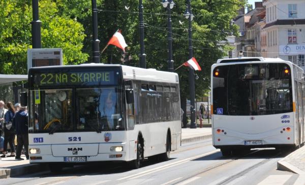 Na zdjęciu autobusy miejskie na węźle przesiadkowym w alei Solidarności, obok na słupach zawieszona flaga Polski oraz województwa kujawsko-pomorskiego