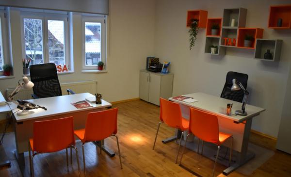 Na zdjęciu pomieszczenie biurowe z biurkami i krzesłami