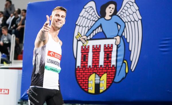 Na zdjęciu Marcin Lewandowski, ambasador halowych mistrzostw Europy, w tle herb Torunia