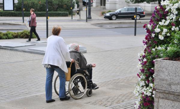 Kobieta prowadząca wózek inwalidzki z osobą niepełnosprawną