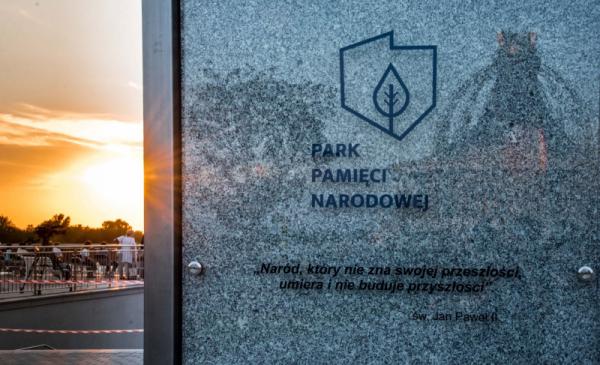Na zdjęciu tablica informacyjna Parku Pamięci Narodowej, w tle zachodące słońce i uczestnicy wydarzenia