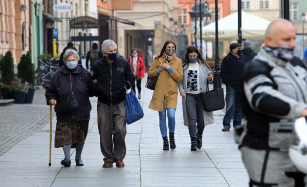 Para seniorów w maskach wśród przechodniów na starówce