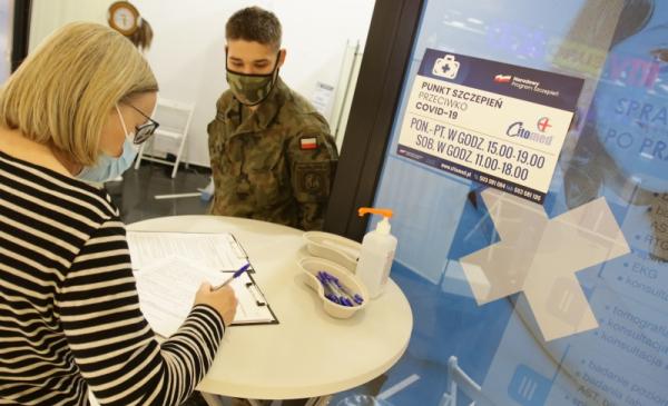 Na zdjęciu osoba wypełnia formularz przed punktem szczepień