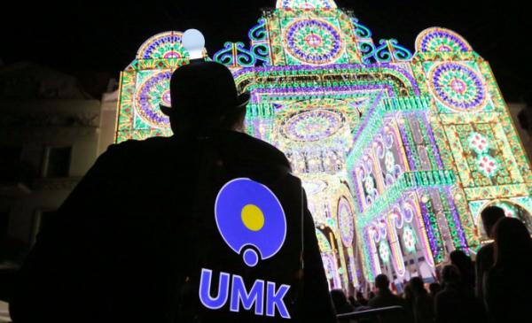 Postać z napisem UMK na tle instalacji Skyway