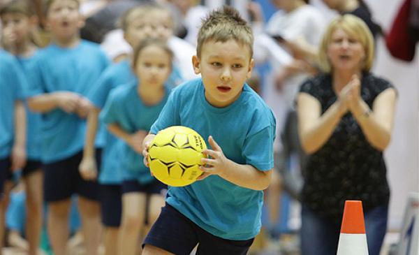 Na zdjęciu widać rywalizację sportową dzieci - chłopiec rzuca piłką