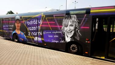 """Na zdjęciu autobus z reklamą """"Podróżuj razem z nami"""" z wizerunkiem Katarzynky Żak i Adriana Miedzińskiego"""