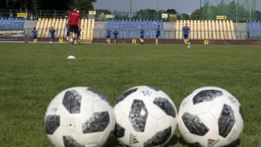 Trzy piłki leżą na murawie stadionu