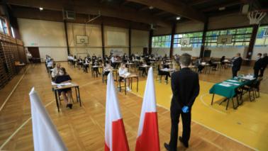 Sala gimnastyczna, w której rozszadzeni w bezpiecznych odległościach uczniowie piszą egzamin maturalny