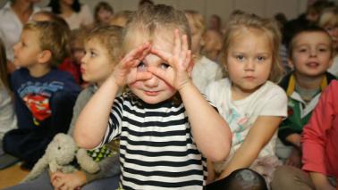 ziewczynka w przedszkolu patrząca przez dłonie zwinięte w okulary na tle grupy przedszkolaków