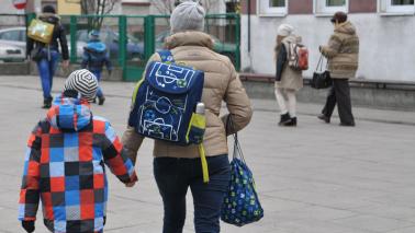 Matka prowadząca dziecko z tornistrem