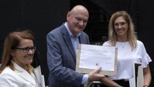 Prezydent Michał Zaleski wręcza symboliczny czek zwycięskiej szkole