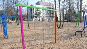 Na zdjęciu widać sprzęty na placu zabaw z piaszczystym podłożem