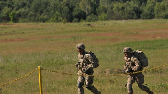 Dwóch żołnierzy biegnie po łące na terenie poligonu