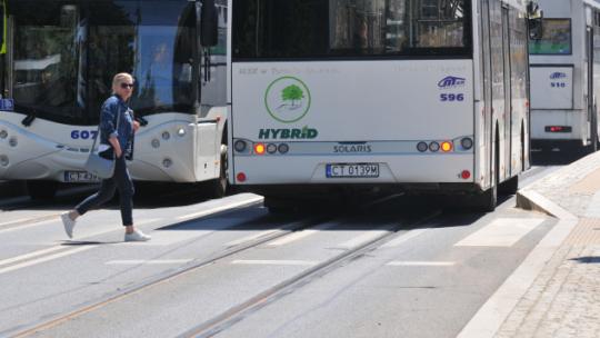 Na zdjęciu: autobusy MZK i przechodząca kobieta na przejściu dla pieszych