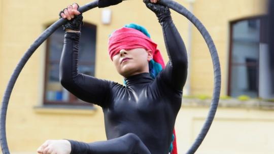 Akrobatka z kołem cyrkowym w przepasce na oczach