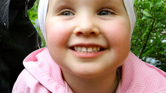 Dziecko uśmiecha się, pojazując zęby