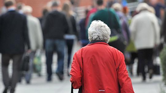 Na zdjęciu seniorka w czerwonej kurtce idzie chodnikiem