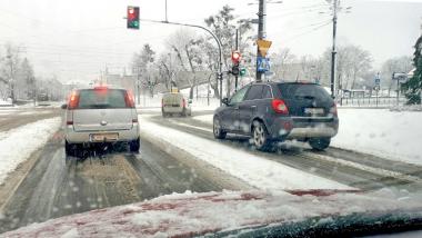 Na zdjęciu samochody stoją na skrzyżowaniu, pada śnieg