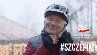 Usmiechnięty mężczyzna zapina kask rowerowy - plakat zachęcający do szczepień przeciwko COVID-19