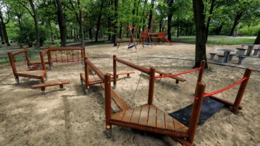 Drewniane sprzęty na placu zabaw na podłożu piaszczystym, wokół rosną drzewa