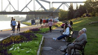 Na zdjęciu osoby siedzą na Bulwarze Filadelfijskim, w tle most im. marsz. Józefa Piłsudskiego