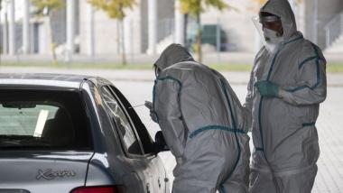 Na zdjęciu widać osoby ubrane w kombinezony ochronne pochylające się nad otwartym oknem samochodu w celu pobrania wymazu