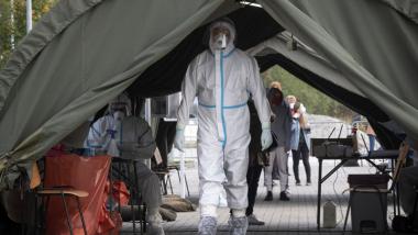 Na zdjęciu widać służby medyczne w specjalnych białych kombinezonach w namiocie, gdzie wykonywane są testy