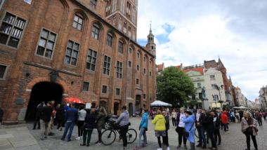 Na zdjęciu osoby czekają w kolejce na szczepienie przed Ratuszem Staromiejskim