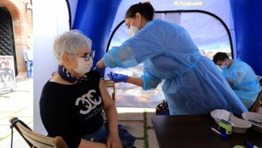 Na zdjęciu pielęgniarka wstrzykuje szczepionkę kobiecie