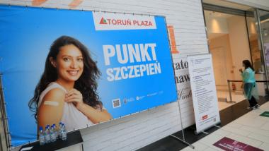 Na zdjęciu baner z uśmiechniętą kobietą i napisem Punkt Szczepień Toruń Plaza