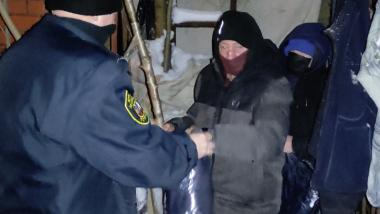 Strażnik miejski wręcza śpiwór osobie bezdomnej
