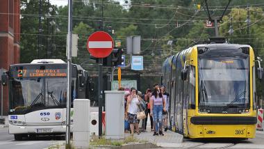 Ludzie w maseczkach na tle tramwaju i autobusu