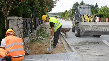 Na zdjęciu widac robotników pracujących przy budowie drogi