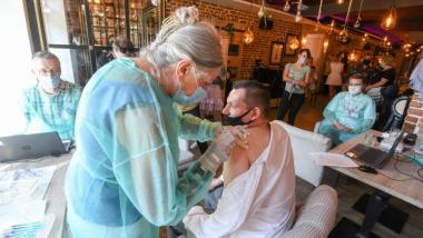 Na zdjęciu pielęgniarka szczepi mężczyznę w restauracji