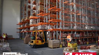 W zakładzie produkcyjnym pracownicy na wózkach widłowych przewożą palety, obok stoją ogromne regały