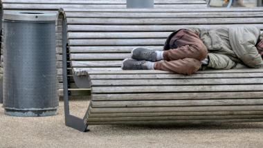 Na zdjęciu osoba leży na ławce