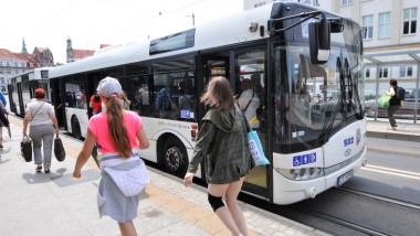 Na zdjęciu osoby idą obok stojącego autobusu