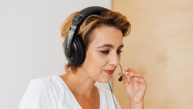 Na zdjęciu kobieta ze słuchawkami z mikrofonem