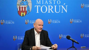 Prezydent Michał Zaleski podczas zdalnej sesji Rady Miasta Torunia, w tle herb miasta